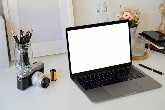 Simulacros de laptop en mesa blanca, espacio de trabajo creativo
