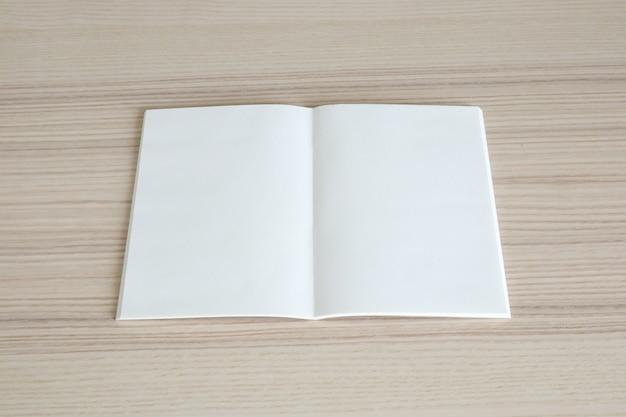Simulacros de libro de papel abierto en blanco sobre fondo de mesa de madera