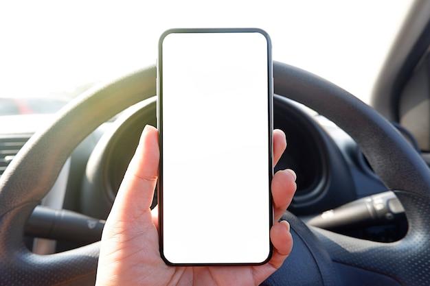 Simulacros de mano del conductor sosteniendo el teléfono en pantalla clara vacía del coche para el texto