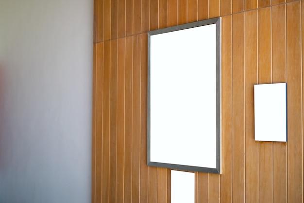 Simulacros de marco de póster en blanco colgado en la pared de madera en la habitación.