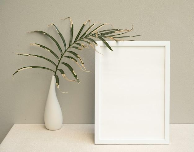 Simulacros de marco de póster y hojas de palma secas en un hermoso jarrón de cerámica blanca sobre una mesa de tonos tierra y una superficie de pared de cemento