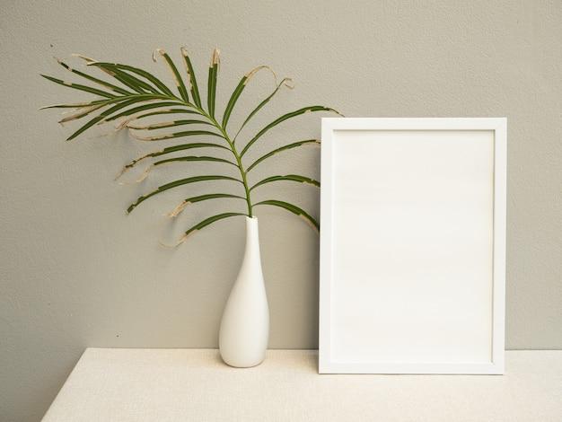 Simulacros de marco de póster y hojas de palma secas en un jarrón de cerámica blanca sobre una superficie de tono tierra