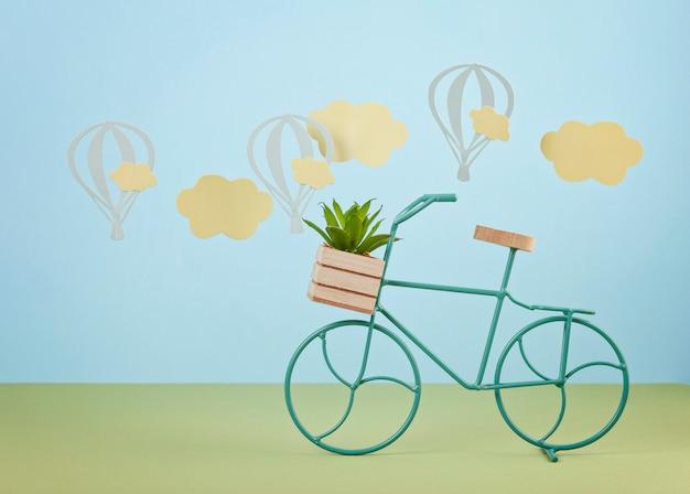 Simulacros con nubes de papel y globos volando sobre el fondo azul pastel y la bicicleta de juguete