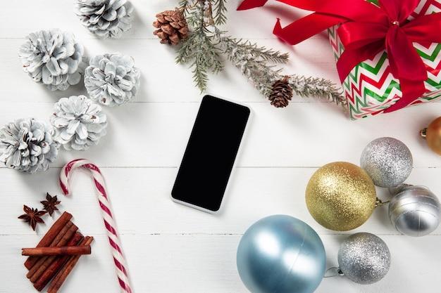 Simulacros de la pantalla vacía en blanco del smartphone en la pared de madera blanca con coloridos regalos y decoración navideña.