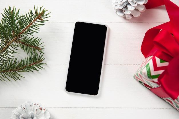 Simulacros de pantalla vacía en blanco del teléfono inteligente en la mesa de madera blanca