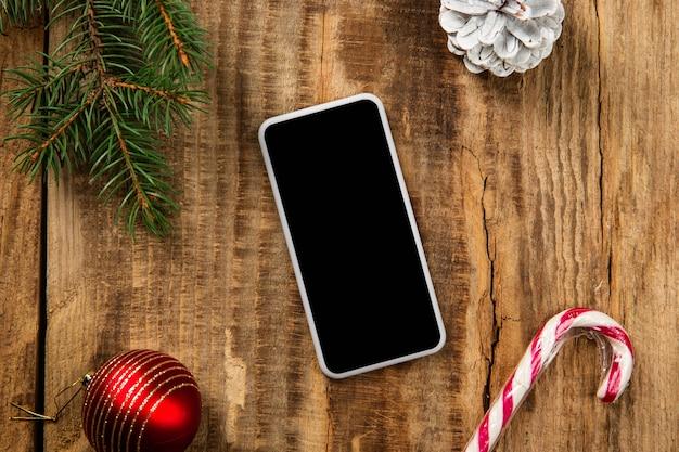 Simulacros de pantalla vacía en blanco del teléfono inteligente en la mesa de madera