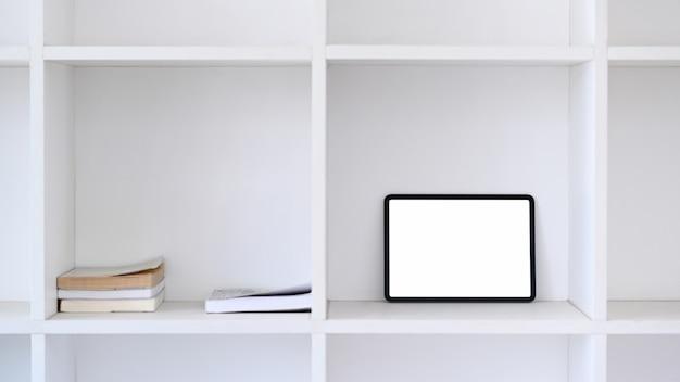 Simulacros de tableta digital con pantalla en blanco en la estantería de libros blancos.