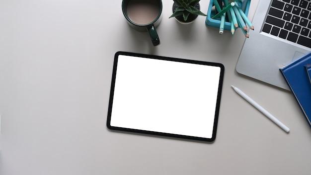 Simulacros de tableta digital con pantalla vacía, portátil, papelería y taza de café en la mesa blanca. vista superior.