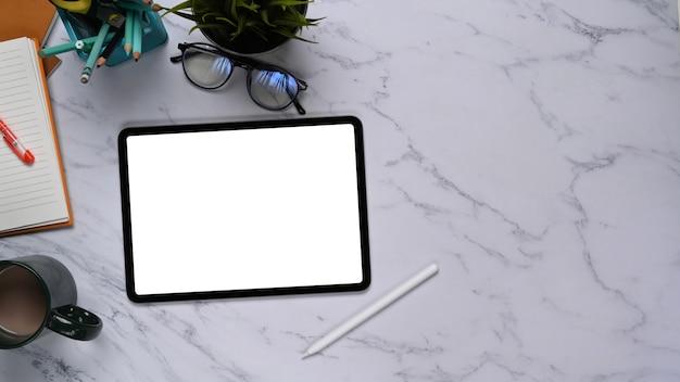 Simulacros de tableta digital con pantalla vacía, vasos, papelería y taza de café en la mesa de mármol. vista superior.