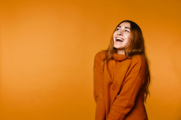 Sinceramente sonriente pelirroja mujer caucásica vestida con jersey de lana
