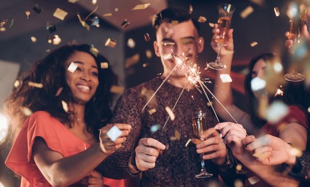 Sinceras emociones amigos multirraciales celebran año nuevo y sostienen luces de bengala y vasos con bebida