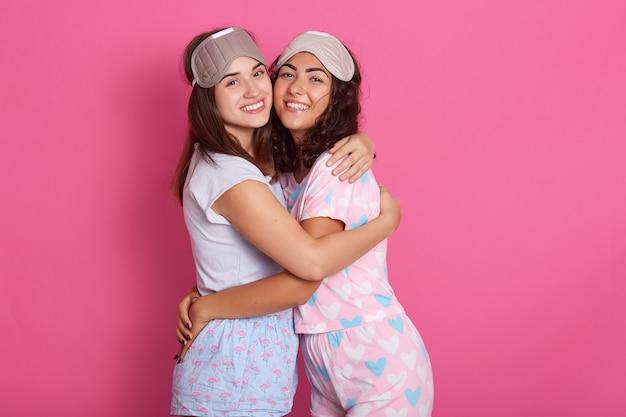 Sinceras hermosas amigas posando aisladas en rosa, abrazándose, sonriendo