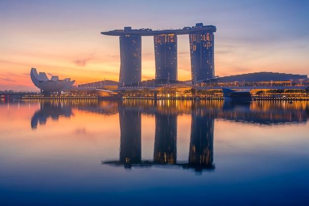 Singapur. temprano en la mañana en marina bay. el sol se pondrá detrás de los edificios del hotel en forma de barco.