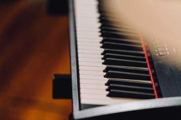 Sintetizador electrónico de teclado musical con teclas blancas y negras en estudio de grabación.