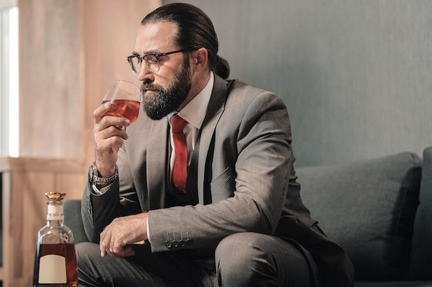 Sintiéndose nervioso. hombre de negocios de pelo oscuro bebiendo una copa de coñac mientras se siente nervioso y agotado