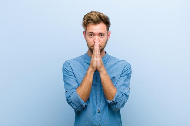 Sintiéndose preocupado, esperanzado y religioso, rezando fielmente con las palmas presionadas, pidiendo perdón