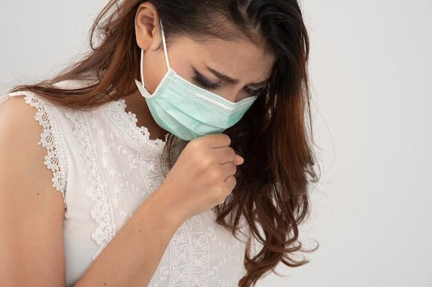 Síntoma de resfriado o alergia a la gripe, enferma joven asiática estornudando en máscara aislar en blanco
