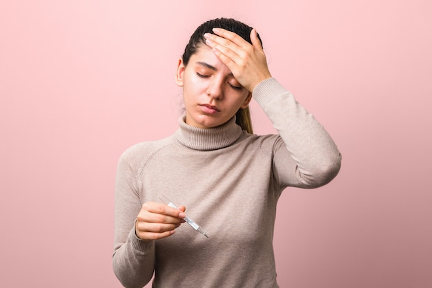Síntomas de coronavirus. mujer con fiebre y dolor de cabeza con termómetro buscando desesperado contra el fondo azul.