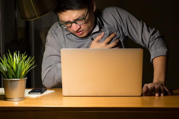 Síntomas de enfermedad cardíaca durante el horario nocturno en la oficina, trabajando hasta tarde y concepto saludable