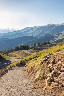 Sinuoso sendero de montaña va cerca de las coloridas montañas. día soleado en un valle de montaña. cáucaso del norte, rusia