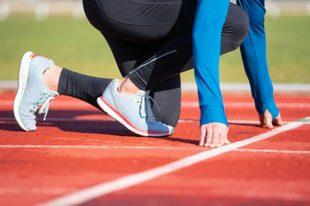 Sirva al atleta en la línea de salida de una pista de atletismo en el estadio, cierre para arriba.