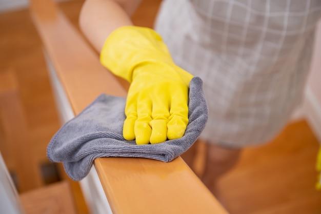 Sirva la limpieza de la barandilla de la escalera usando alcohol y solución de limpieza líquida. concepto de protección covid-19, siempre equipos de limpieza en la vida diaria. saneamiento y asistencia sanitaria.