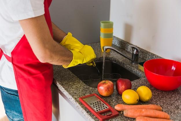 Sirva la mano que lava la cuchara en la cocina