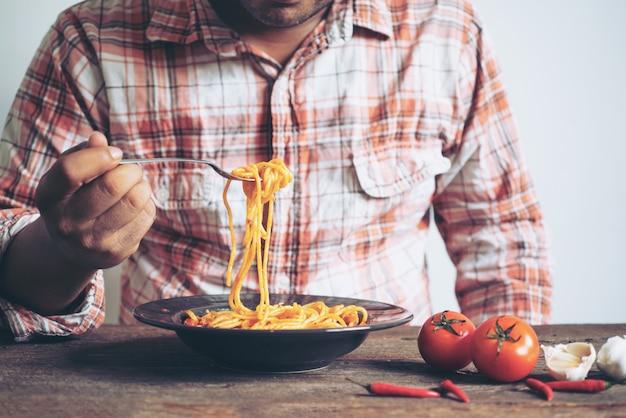 Sirva la mano que sostiene la bifurcación de las pastas en el plato en la tabla de madera en el foco selectivo del restaurante