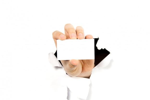 Sirva la mano que sostiene la tarjeta de visita blanca a través del agujero en pared o papel blanco roto.