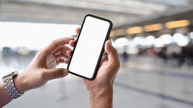 Sirva la mano que sostiene el teléfono elegante móvil de la pantalla en blanco en fondo del contador de la terminal del aeropuerto