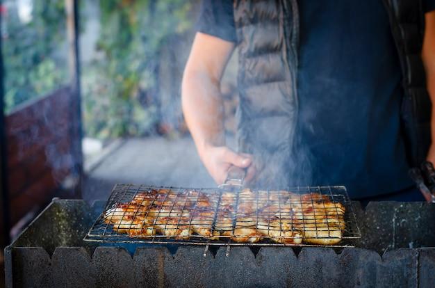 Sirva las manos que sostienen una red de la parrilla con las alas de pollo sobre el carbón de leña.