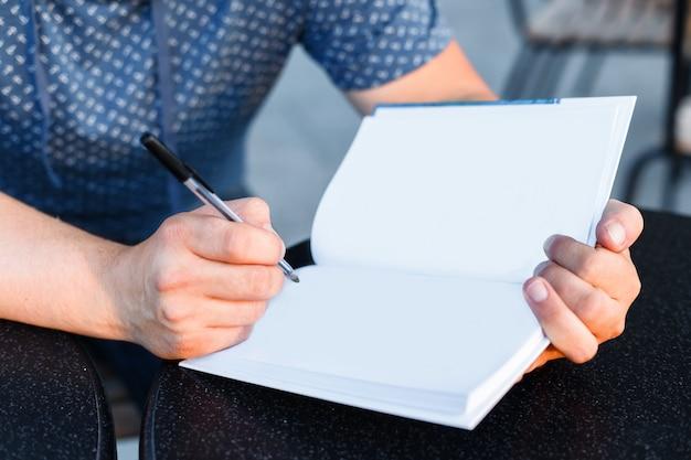 Sirva sentarse en la tabla en un café, escribiendo en las páginas vacías blancas del primer abierto del libro.