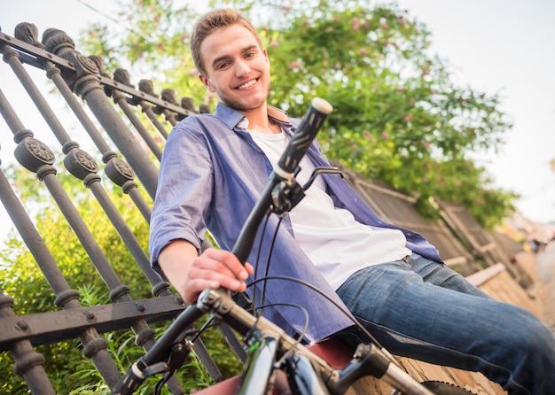 Sirva la situación con la bicicleta en la calle de la ciudad cerca de la cerca.