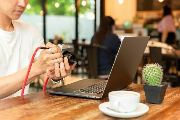 Sirva sostener la cámara mirrorless digital que comprueba la foto con el ordenador portátil en la tabla.