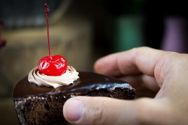 Sirva sostener el pedazo de torta de chocolate deliciosa, primer.