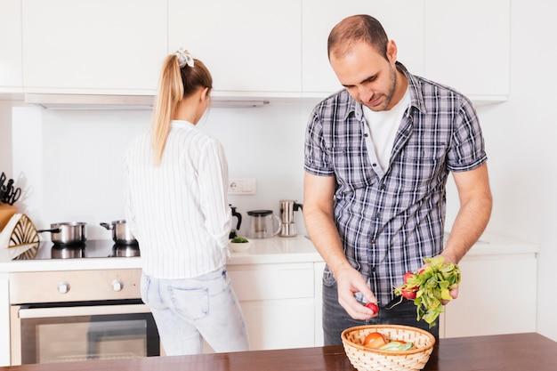 Sirva sostener el rábano rojo sano fresco con su novia que se coloca en el fondo