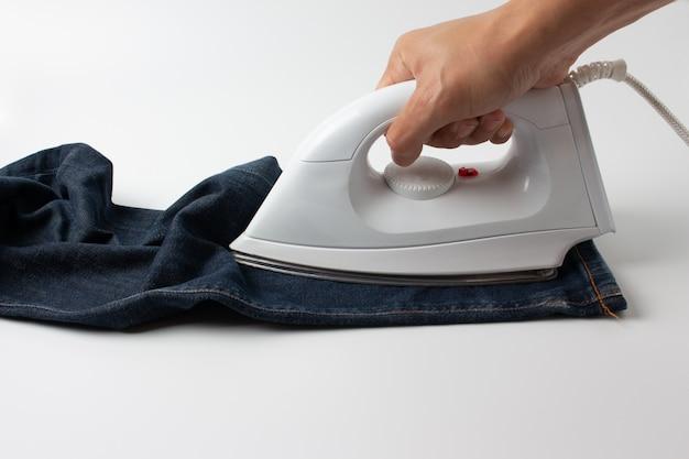 Sirva los tejanos que planchan en la tabla blanca en el cuarto.