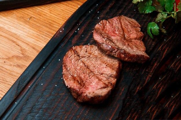 Se sirven porciones gruesas y jugosas de filete frito, espolvoreado con sal, sobre una tabla de madera vieja. el plato está listo para servir.
