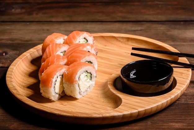 Se sirven varios tipos de sushi. rodillo con salmón, aguacate, pepino. menú de sushi comida japonesa.