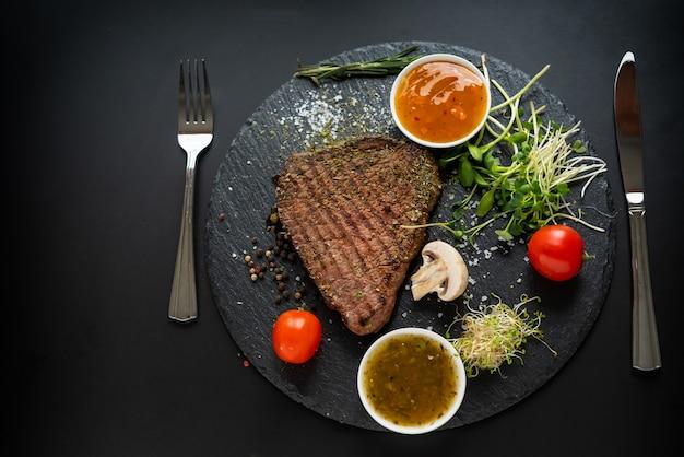 Sirviendo de bistec de ternera a la parrilla sazonada con guarniciones de ensalada y platos de salsa picante visto desde arriba en negro