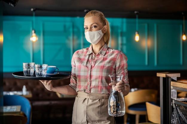 Sirviendo café y agua durante el coronavirus. retrato, de, un, camarera, mujer, con, mascarilla