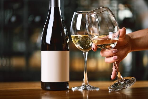 Sirviendo con copas de vino y una botella en la mesa manos levantan una copa de vino