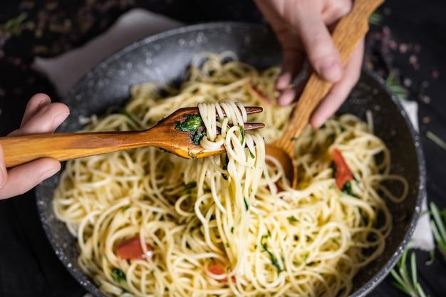 Sirviendo pasta italiana tradicional de una sartén, vista desde arriba. manos masculinas tomando espagueti en cuchara y tenedor, disparó en clave baja