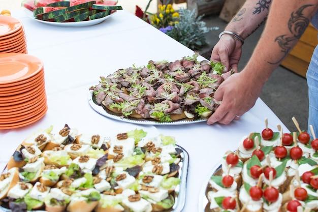 Sirviendo pequeños sándwiches abiertos en fiesta en el jardín