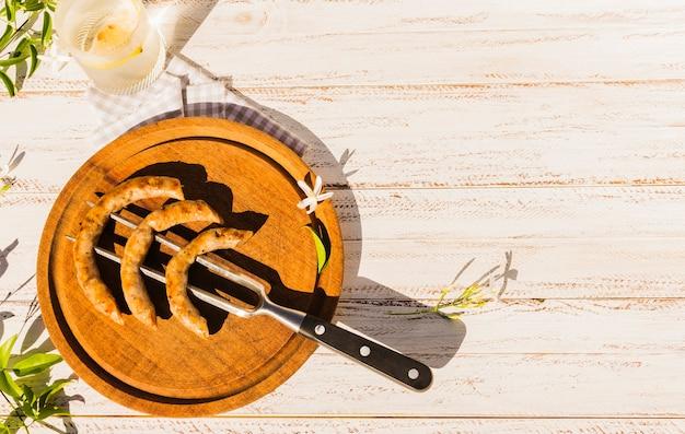 Sirviendo salchichas bávaras colgadas en el tenedor