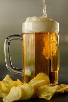 Sirviendo un vaso de cerveza y unas papas fritas