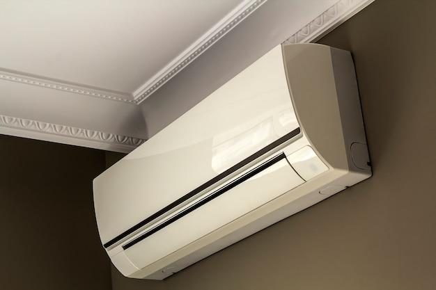 Sistema de aire acondicionado frío en la pared oscura en el interior de la habitación.