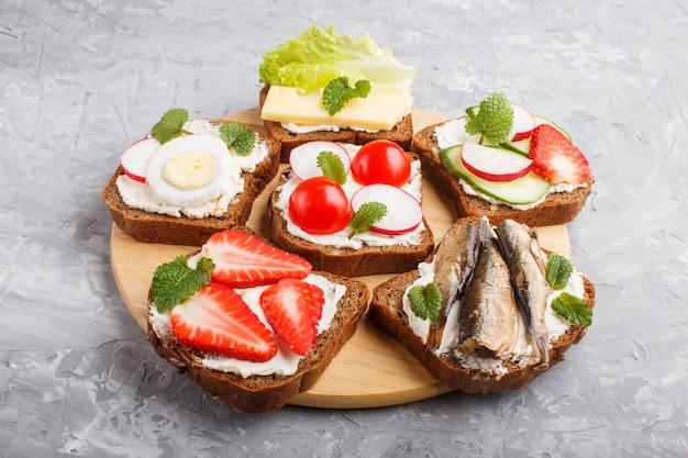 Sistema de diversos bocadillos con queso, el rábano, la lechuga, la fresa, los espadines, los tomates y el pepino en el tablero de madera en un hormigón gris. vista lateral.
