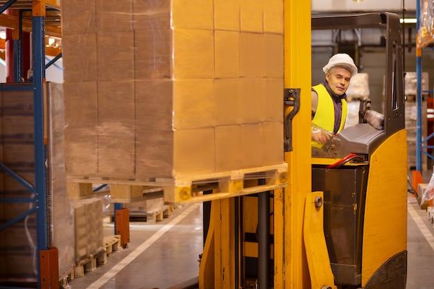 Sistema de entrega. buen hombre inteligente que conduce el vehículo de la máquina mientras trabaja en el almacén