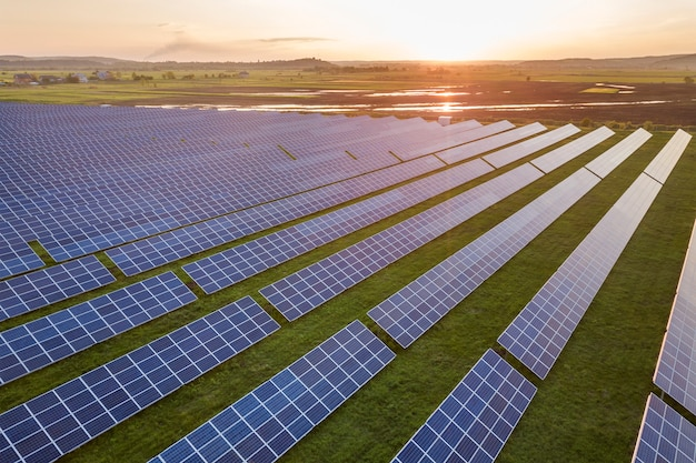 Sistema de paneles fotovoltaicos solares azules que producen energía limpia renovable en el paisaje rural y la puesta del sol